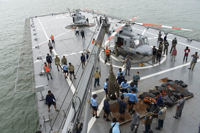 """Indonesian Navy personnel evacuate recovered dead bodies of passengers from AirAsia flight QZ8501, on the the deck of the Indonesian Navy vessel KRI Banda Aceh, at sea January 3, 2015. Ships searching for the wreck of an AirAsia passenger jet that crashed with 162 people on board have pinpointed two """"big objects"""" on the sea floor, the head of Indonesia's search and rescue agency said on Saturday. (Photo by Adek Berry/Reuters)"""