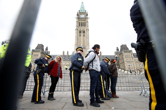 Protestors are detained after crossing a police barricade during a demonstration against the proposed Kinder Morgan pipeline on Parliament Hill in Ottawa, Ontario, Canada, October 24, 2016. (Photo by Chris Wattie/Reuters)