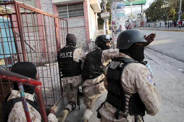 National Police officers secure an area where residents and protesters clashed during a demonstration against the results of the presidential elections in Port-au-Prince, Haiti, November 24, 2015. Haiti's Provisional Electoral Council (CEP) confirmed that government-backed candidate Jovenel Moise will face Jude Celestin, the former head of Haiti's state construction company, in a runoff vote next month. (Photo by Andres Martinez Casares/Reuters)