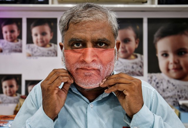 A man tries on a face mask with his portrait printed on it, amid the spread of the coronavirus disease (COVID-19), at a photo studio in Gandhinagar, India, May 27, 2020. (Photo by Amit Dave/Reuters)