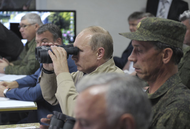 Vladimir Putin uses a pair of binoculars to observe troops in action during a training exercise named Kavkaz 2012 in Krasnodar region September 17, 2012. (Photo by Alexei Druzhinin/Reuters/RIA Novosti)
