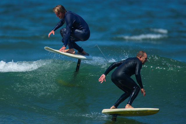 Surfers Jon Foreman and Gary Clisby pass each other as they ride their foil boards on a morning swell of the coast of Carlsbad, California on May 23, 2018. (Photo by Mike Blake/Reuters)