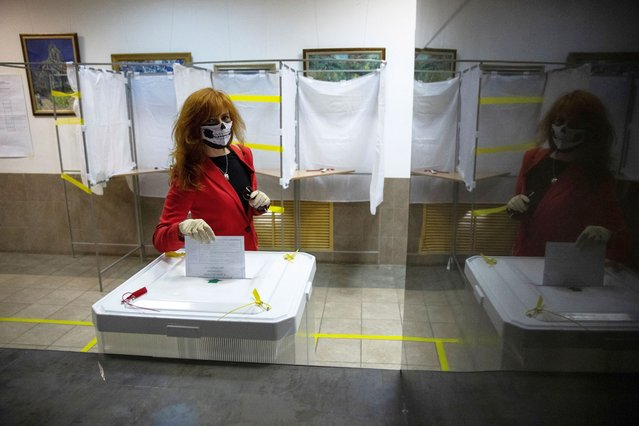 A voter wearing a face mask to protect against coronavirus casts her ballot at a polling station in Moscow, Russia, Monday, June 29, 2020. Polls opened in Russia on June 25 for a week-long vote on a constitutional reform that would allow President Vladimir Putin to stay in power until 2036. (Photo by Pavel Golovkin/AP Photo)