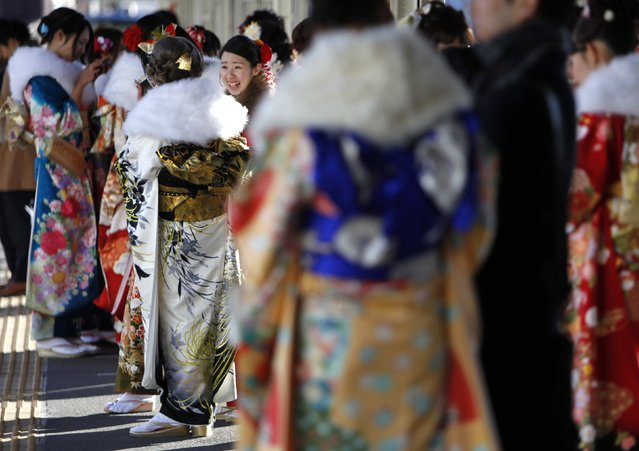 Japanese women in kimonos have a chat at a platform of a train station after a Coming of Age Day celebration ceremony at an amusement park in Tokyo January 12, 2015. (Photo by Yuya Shino/Reuters)