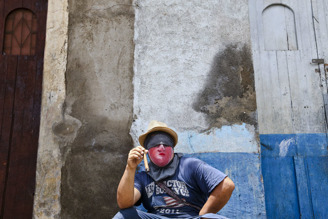 A protester wearing a mask to protect his identity smokes a cigar in the Monimbo neighborhood, in Masaya, Nicaragua, Saturday, June 2, 2018. (Photo by Esteban Felix/AP Photo)