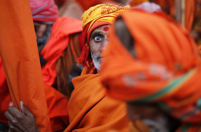 An Indian Sadhu, or Hindu holy man, sits for a community feast at the Sangam, the confluence of the Rivers Ganges, Yamuna and mythical Saraswati, during the annual month-long Magh Mela religious fair in Allahabad, India, Friday, January 16, 2015. (Photo by Rajesh Kumar Singh/AP Photo)