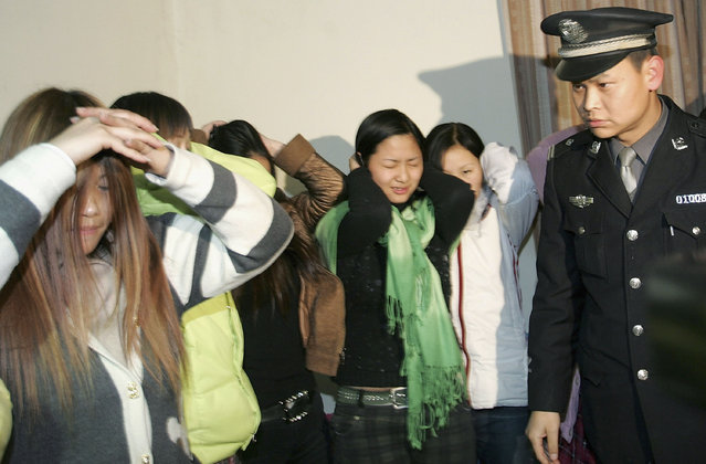 CHENGDU, CHINA - NOVEMBER 23: (CHINA OUT) A policeman guards arrested prostitutes at the Chengdu Municipal Public Security Bureau on November 23, 2005 in Chengdu of Sichuan Province, China. At least 17 prostitutes and whoremasters were arrested during a police operation in Chengdu. Authorities have launched campaigns to crack down on prostitutions in the city. According to state media, male and female prostitution, both of which are illegal in China, are nonetheless widespread. According to a draft guideline released by the Ministry of Health, prostitutes are being made the focus of the ministry's latest efforts to stem the spread of HIV/AIDS. (Photo by China Photos/Getty Images)