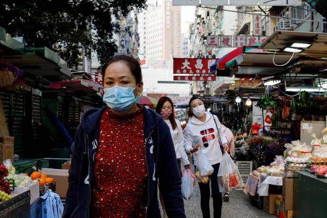 Residents wear face masks as they walk at a wet market at Jordan residential area, where tens of thousands of its residents will be placed in a lockdown to contain a new outbreak of the coronavirus disease (COVID-19), in Hong Kong, China on January 22, 2021. (Photo by Tyrone Siu/Reuters)