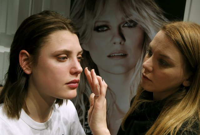 A model has make-up applied while backstage before presenting creations by Charlotte Ronson during Berlin Fashion Week Autumn/Winter 2015 in Berlin January 19, 2015. (Photo by Fabrizio Bensch/Reuters)