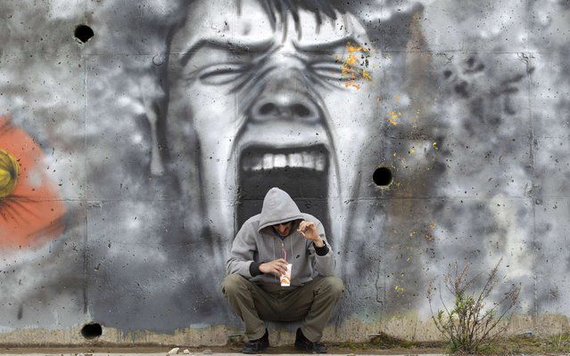 A man drinks coffee in front of a mural near the coastal town of Kalamatta in the Messinia area of Greece in this March 23, 2012 file photo. (Photo by Cathal McNaughton/Reuters)