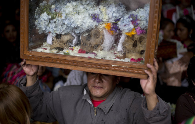 """A man balances a wooden framed glass case on head containing decorated human skulls or """"natitas"""", inside the cementerio General chapel during the Natitas Festival celebrations in La Paz, Bolivia, Tuesday, November 8, 2016. (Photo by Juan Karita/AP Photo)"""