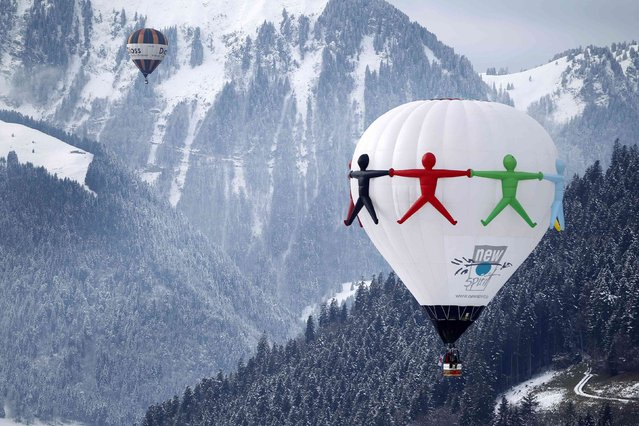 Balloons fly during the 37th International Hot Air Balloon Week in Chateau-d'Oex, January 24, 2015. (Photo by Pierre Albouy/Reuters)