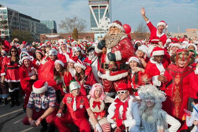 A crowd of people dressed as Santa gather for a group photo during the annual SantaCon pub crawl December 12, 2015 in the Brooklyn borough of New York City. (Photo by Stephanie Keith/Getty Images)
