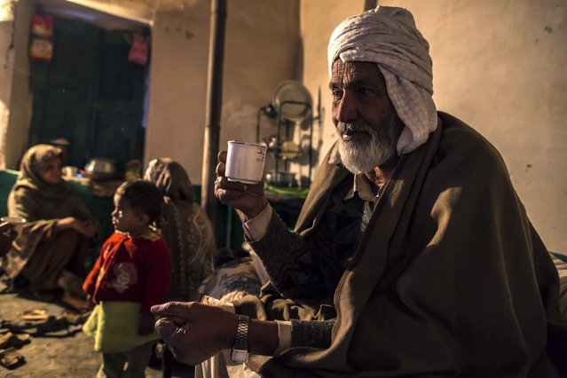 A man holds a cup of tea while he sits with his family at their house on Margalla Hills in Islamabad January 22, 2015. (Photo by Zohra Bensemra/Reuters)