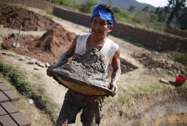 A worker carries mud used to make bricks at a brick factory in Tixtla, on the outskirts of Chilpancingo, in the Guerrero state, January 26, 2015. (Photo by Jorge Dan Lopez/Reuters)