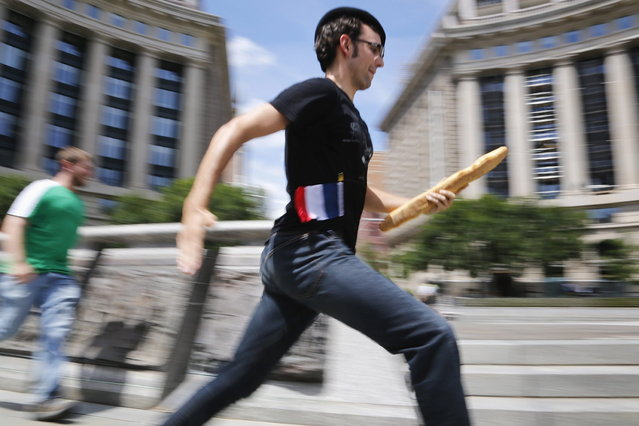 """People compete in a lighthearted French baguette relay race as part of a Bastille Day promotion at the La Maison Paul restaurant in Washington, July 14, 2013. The restaurant says the bread in their Washington restaurants comes from a """"mother dough"""" starter brought directly from Lille, France. (Photo by Jonathan Ernst/Reuters)"""