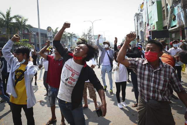 Protesters shout slogans during a protest against the military coup in Mandalay, Myanmar, Sunday, February 28, 2021. Police fired tear gas and water cannons and there were reports of gunfire Sunday in Myanmar's largest city Yangon where another anti-coup protest was underway with scores of students and other demonstrators hauled away in police trucks. (Photo by AP Photo/Stringer)