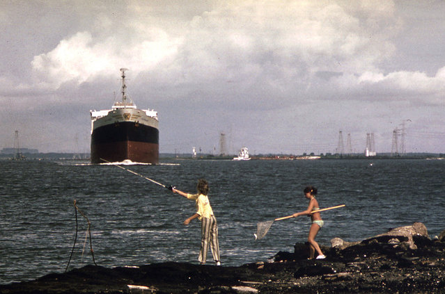 A freighter moves slowly up the Houston ship channel as girls fish from the shore, September 1973. Oil derricks are visible in the background. (Photo by Blair Pittman/NARA via The Atlantic)