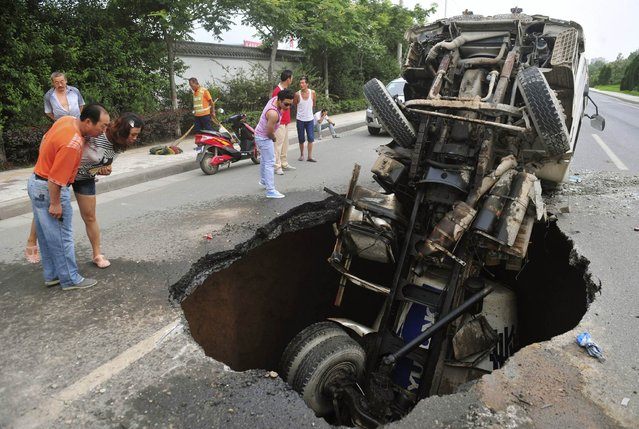 People look at a tanker after it fell into a caved-in area on a road in Xi'an, Shaanxi province, July 27, 2013. No casualty was reported in the accident, according to local media. (Photo by Reuters/Stringer)
