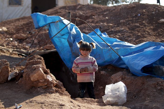 An internally displaced Syrian girl stands at the entrance of her makeshift shelter that is an underground cave in Om al-Seer, southern Idlib countryside, Syria December 26, 2015. (Photo by Khalil Ashawi/Reuters)
