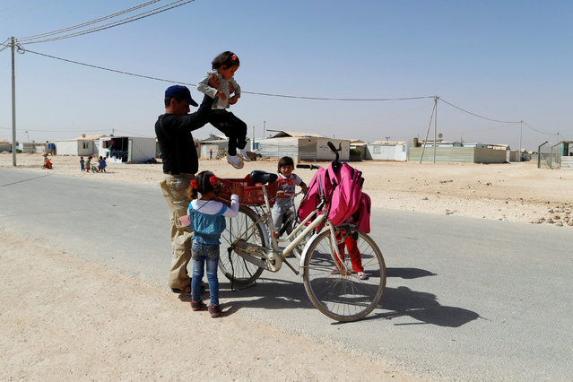 A Syrian refugee man fetches his children after school in Al-Zaatari refugee camp near the border with Syria, in Mafraq, Jordan October 9, 2016. (Photo by Ammar Awad/Reuters)