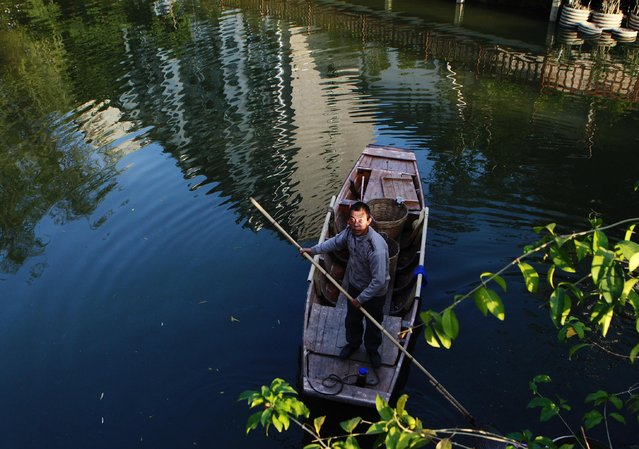 A man picks up garbage from a canal in Guangzhou, Guangdong province, January 26, 2015. (Photo by Alex Lee/Reuters)