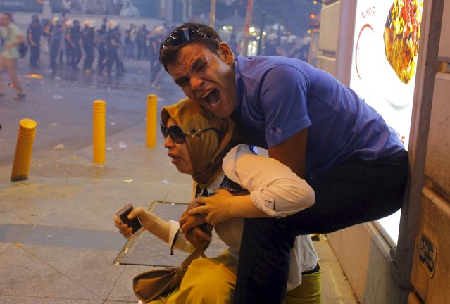 A couple, affected by tear gas used by riot police to disperse demonstrators, reacts in central Istanbul, Turkey, July 20, 2015. (Photo by Huseyin Aldemir/Reuters)