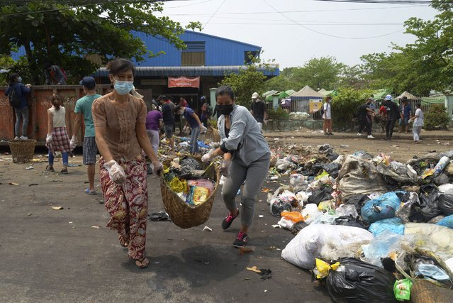 """Anti-coup protesters use garbage to block a road as a form of """"silent protest"""" in Yangon, Myanmar on Tuesday, March 30, 2021. At least 510 protesters have been killed since the coup, as of Tuesday, according to Myanmar's Assistance Association for Political Prisoners, which says the actual toll is likely much higher. (Photo by AP Photo/Stringer)"""