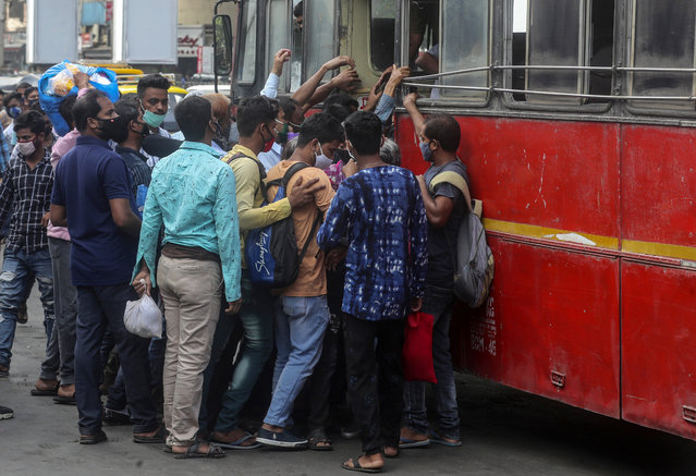 People wearing masks board a bus in Mumbai, India, Monday, April 5, 2021. India reported its biggest single-day spike in confirmed coronavirus cases since the pandemic began Monday, and officials in the hard-hit state home to Mumbai are returning to the closure of some businesses and places of worship in a bid to slow the spread. (Photo by Rafiq Maqbool/AP Photo)
