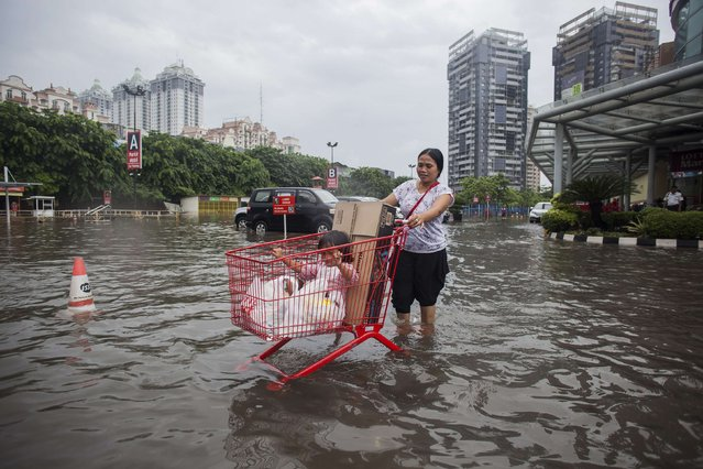 A mother uses a shopping cart to transport her child and groceries through a flooded parking lot at a mall in Kelapa Gading, North Jakarta, February 11, 2015 in this photo taken by Antara Foto. Heavy seasonal rains this week have caused flooding in many parts of the nation's capital. (Photo by Sigid Kurniawan/Reuters/Antara Foto)