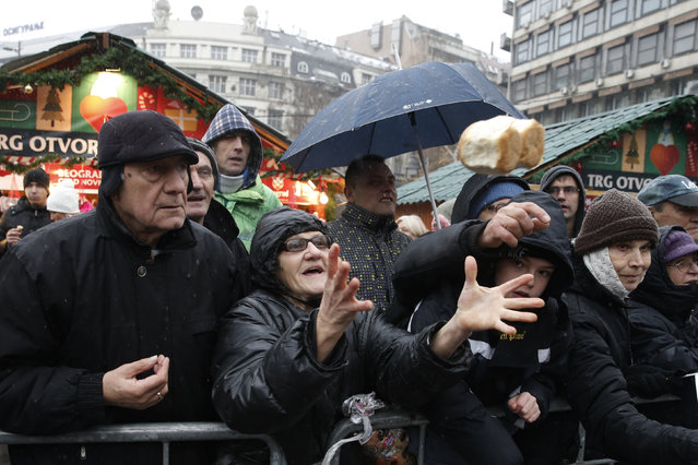 People gather to receive a piece of traditional Christmas bread, marking the Orthodox Christmas Day festivities in Belgrade, Serbia January 7, 2016. Serbian Orthodox believers celebrate Christmas on January 7, according to the Julian calendar. (Photo by Marko Djurica/Reuters)