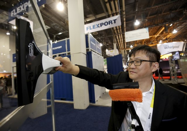 Po Feng Peng of China uses a Grun Luft window vacuum to clean a window at the Xiamen Voke Health Technology booth during the 2016 CES trade show in Las Vegas, Nevada January 8, 2016. The combination vacuum and squeegee increases efficiency, a representative said. (Photo by Steve Marcus/Reuters)