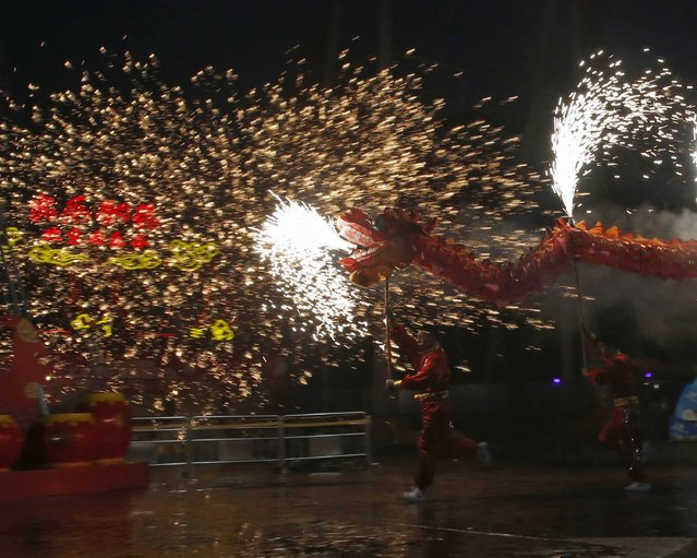Dancers perform a fire dragon dance in the shower of molten iron spewing firework-like sparks during a folk art performance to celebrate traditional Chinese Spring Festival on Chinese Lunar New Year at the Happy Valley amusement park in Beijing February 19, 2015. (Photo by Kim Kyung-Hoon/Reuters)