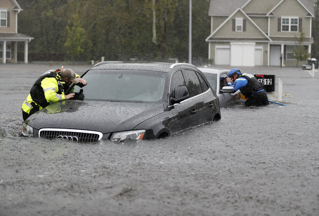 Members of the North Carolina Task Force urban search and rescue team check cars in a flooded neighborhood looking for residents who stayed behind as Florence continues to dump heavy rain in Fayetteville, N.C., Sunday, September 16, 2018. (Photo by David Goldman/AP Photo)