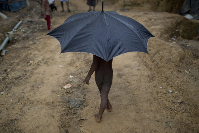 In this June 25, 2018, file photo, a Rohingya child refugee carries an umbrella as he walks through Kutupalong refugee camp in Bangladesh. (Photo by Wong Maye-E/AP Photo)