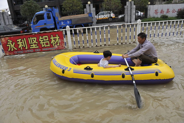 Residents make their way through a flooded street on an inflatable boat in disaster-hit Cangnan county of Wenzhou, east China's Zhejiang province,  on October 7, 2013, where more than 1,200 homes collapsed and damages amounted to hundreds of millions of yuan. Typhoon Fitow barrelled into China's east coast, packing winds of more than 200 kilometres (125 miles) an hour, after hundreds of thousands of people were evacuated and bullet train services were suspended. At least three people were reported killed, all of them near the city of Wenzhou in Zhejiang province, the state broadcaster CCTV said. (Photo by AFP Photo)