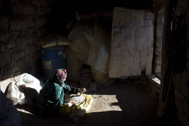 A woman prepares wheat bread in her doorway in Ait Sghir village in the High Atlas region of Morocco February 14, 2015. (Photo by Youssef Boudlal/Reuters)