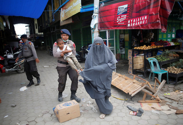 A police officer carries a child as he helps a woman leave a covered market, after an aftershock was felt, following this week's strong earthquake in Meureudu,  Pidie Jaya, Aceh province, Indonesia December 9, 2016. (Photo by Darren Whiteside/Reuters)