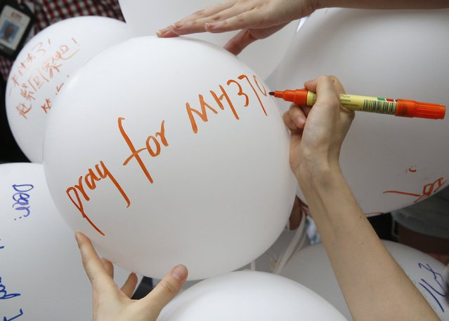 A relative of a passenger aboard missing Malaysia Airlines flight MH370 writes on a balloon at a remembrance event on the one year anniversary of its disappearance in Kuala Lumpur, March 8, 2015. Malaysia's Prime Minister Najib Razak said on Sunday Malaysia remains committed to the search for the missing MH370 jetliner a year after it vanished without trace and he is hopeful it will be found. REUTERS/Olivia Harris