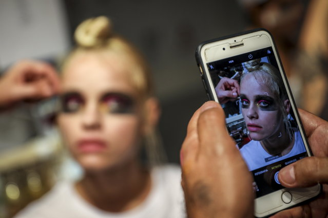 A model is photographed as she gets her make up done backstage prior to Dino Alves's runway show during the 51st Lisbon Fashion Week, in Lisbon, Portugal, 14 October 2018. (Photo by Jose Sena Goulao/EPA/EFE)