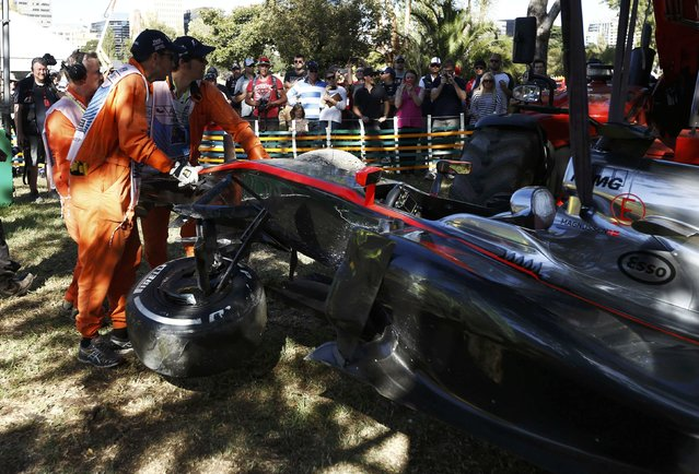 Course officials remove the car of McLaren Formula One driver Kevin Magnussen of Denmark after he crashed during the second practice session of the Australian F1 Grand Prix at the Albert Park circuit in Melbourne March 13, 2015.   REUTERS/Jason Reed