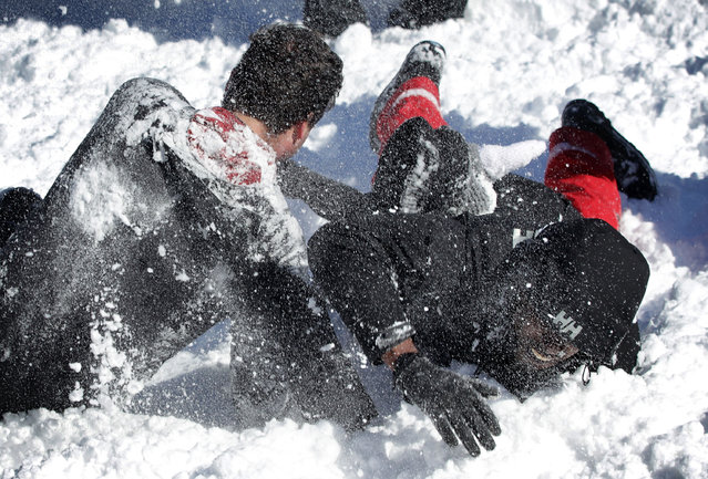 A man tackles another man as they participate in a snowball fight at Dupont Circle January 24, 2016 in Washington, DC. (Photo by Alex Wong/Getty Images)