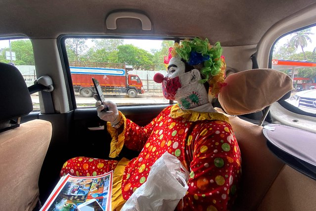Social worker volunteer Ashok Kurmi, dressed as a clown checks his mobile phone while sitting inside a car before going into slums to start a sanitation work and spread awareness to follow the Covid-19 coronavirus safety protocols, in Mumbai on June 2, 2021. (Photo by Indranil Mukherjee/AFP Photo)