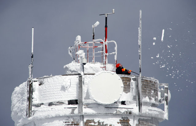 In this Tuesday, March 10, 2015 photo, a scientist knocks rime ice off the surface of weather instruments on top of the Mount Washington Observatory at the summit of Mount Washington in New Hampshire. (Photo by Robert F. Bukaty/AP Photo)