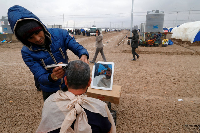 A displaced man who fled the Islamic State stronghold of Mosul, gets a haircut at Khazer camp, Iraq December 19, 2016. (Photo by Ammar Awad/Reuters)