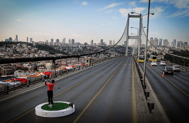 Tiger Woods makes a shot from East to West on the iconic Bosporus Bridge that separates the continents of Europe and Asia, in Istanbul, Turkey, to promote the Turkish Airlines Open, on November 5, 2013. (Photo by Associated Press)