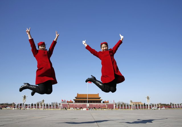 Hotel guides jump as they pose for photographs in front of the Tiananmen Gate and the giant portrait of Chinese late chairman Mao Zedong, near the Great Hall of the People during the third plenary meeting of Chinese People's Political Consultative Conference (CPPCC) in Beijing, March 11, 2015. (Photo by Kim Kyung-Hoon/Reuters)