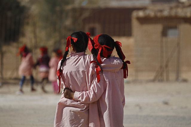 ALGERIA: Indigenous Sahrawi girls hug each other beside their school in a refugee camp of Boudjdour in Tindouf, southern Algeria March 3, 2016. (Photo by Zohra Bensemra/Reuters)
