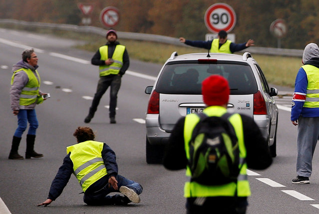 A car drives through a blockade as protesters wearing yellow vests, a symbol of a French drivers' protest against higher fuel prices, block a road in Donges, France November 17, 2018. (Photo by Stephane Mahe/Reuters)