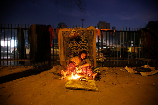 A woman warms herself by a fire along a road on a cold winter evening in New Delhi, India, December 28, 2016. (Photo by Adnan Abidi/Reuters)